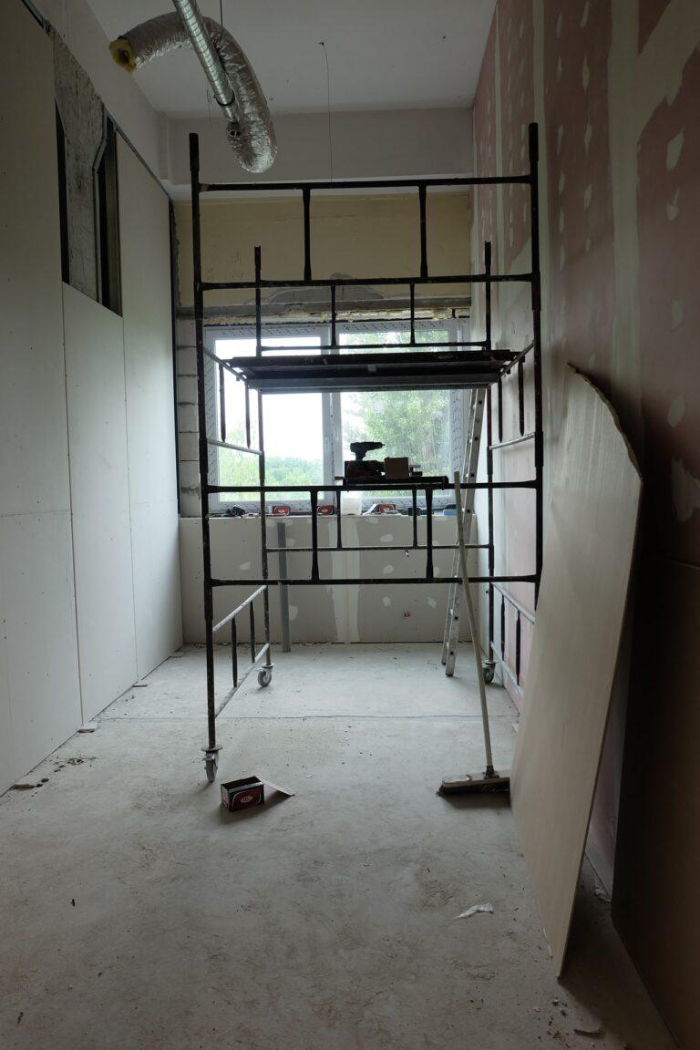 Na zdjęciu widac pokój w remoncie na środku znajduje się rusztowanie o ściane oparta jest płyta na końcu pokoju jest okno