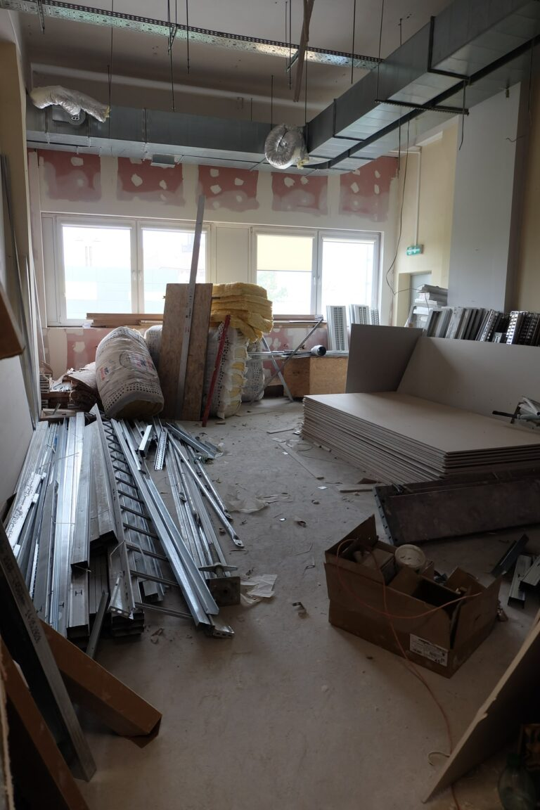 Na zdjęciu znajduje się duży pokój w remoncie. W całym pokoju porozstawiane są materiały budowlane takie jak płyty, wełna i inne.