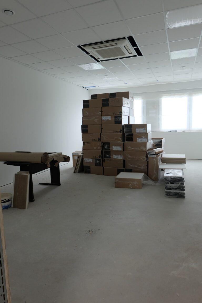Na zdjęciu widać pokój z białymi ścianami, który jest w remoncie. Na środku postawione są duże kartony.