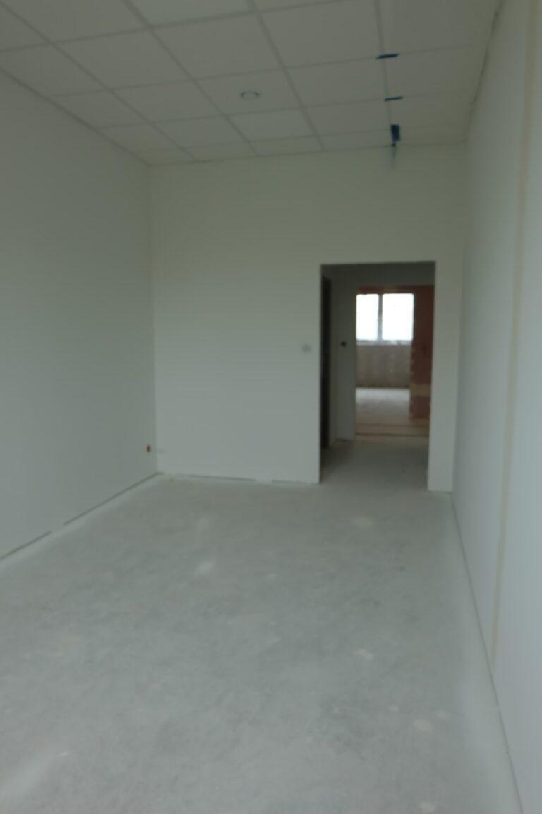 Na zdjęciu jest pokój z białymi ścianami i wejściem bez drzwi. Pokój jest w remoncie.