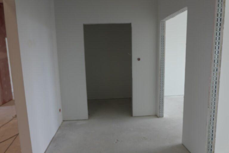 Na zdjęciu widać pokój w remoncie. Ściany są białe. Na wprost i po prawej stronie znajdują się wejścia do pokoi, w ktorych nie ma wstawionych drzwi.