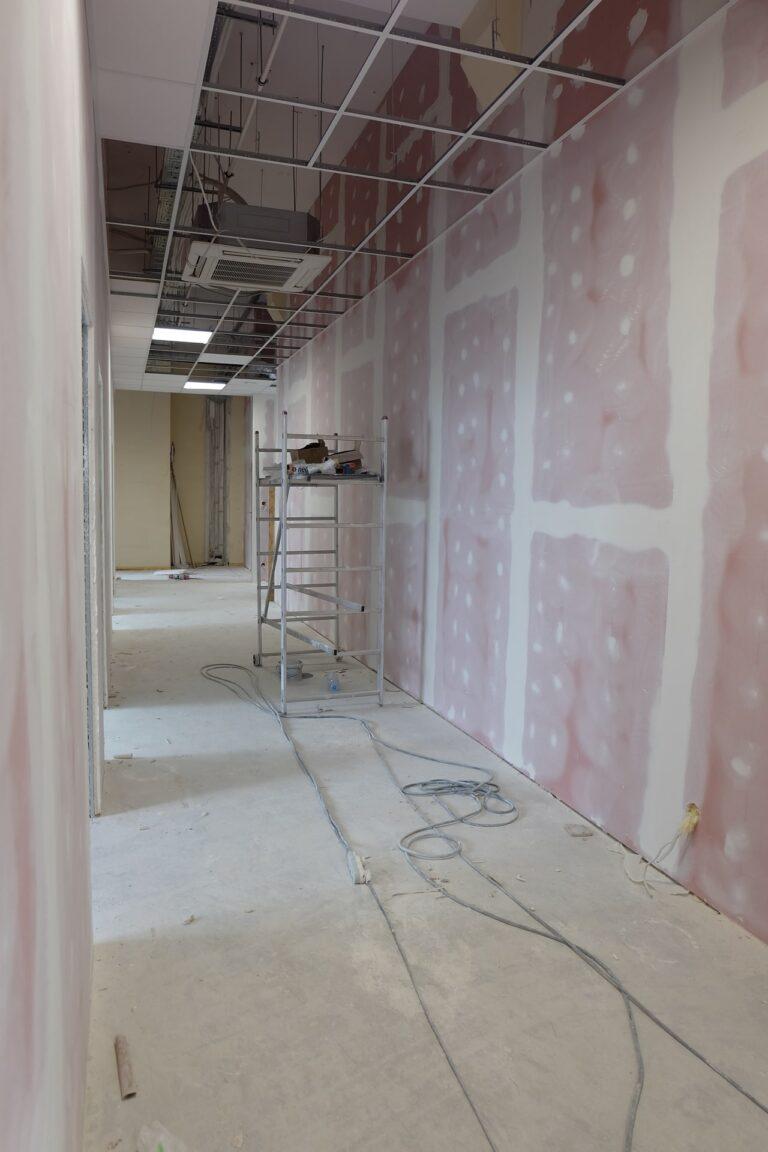 Na zdjęciu widać korytarz w czasie remontu. ściany są w gładzi. Na środku rozstawione jest rusztowanie.
