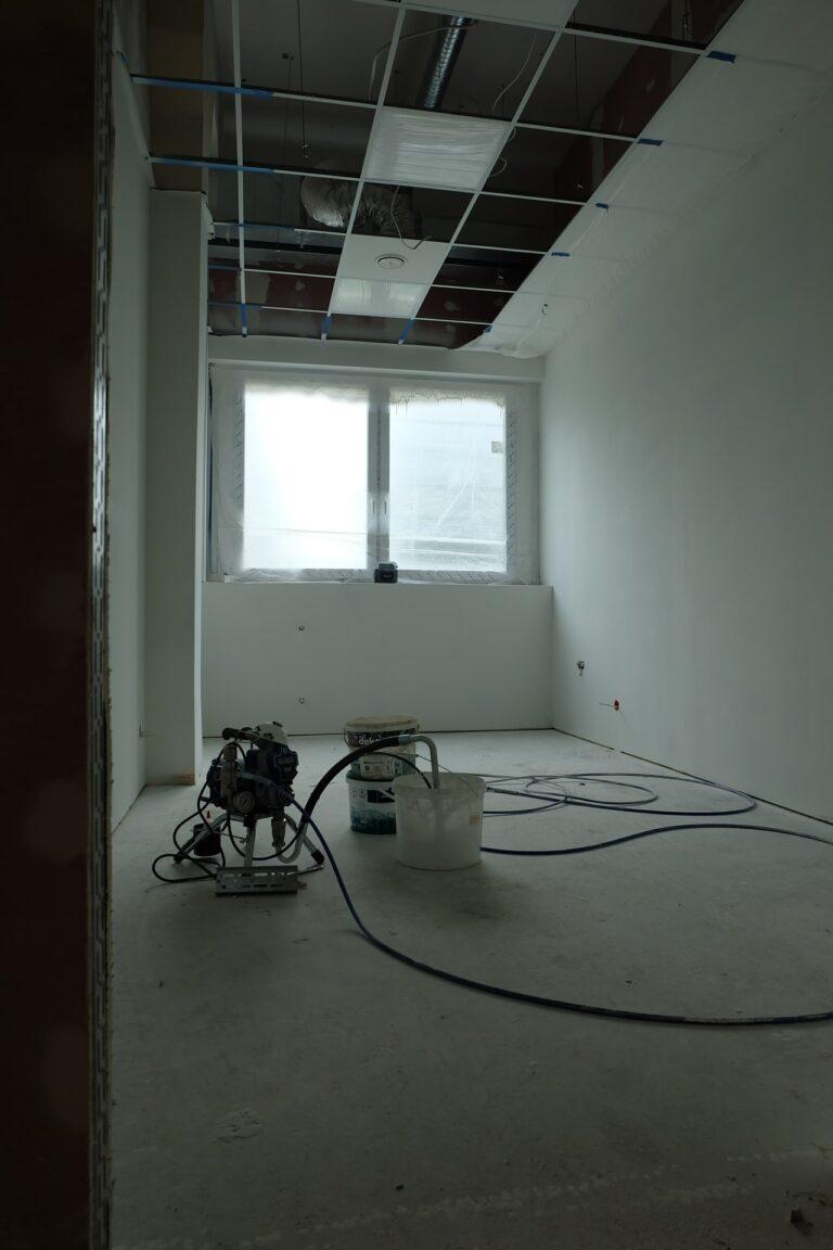 Na zdjęciu jest pokój z białymi ścianami i oknami wzdłuż jednej z nich. Pokój jest w remoncie. Sufit jest wykładany. Na środku są wiaderka i sprzęt remontowy.