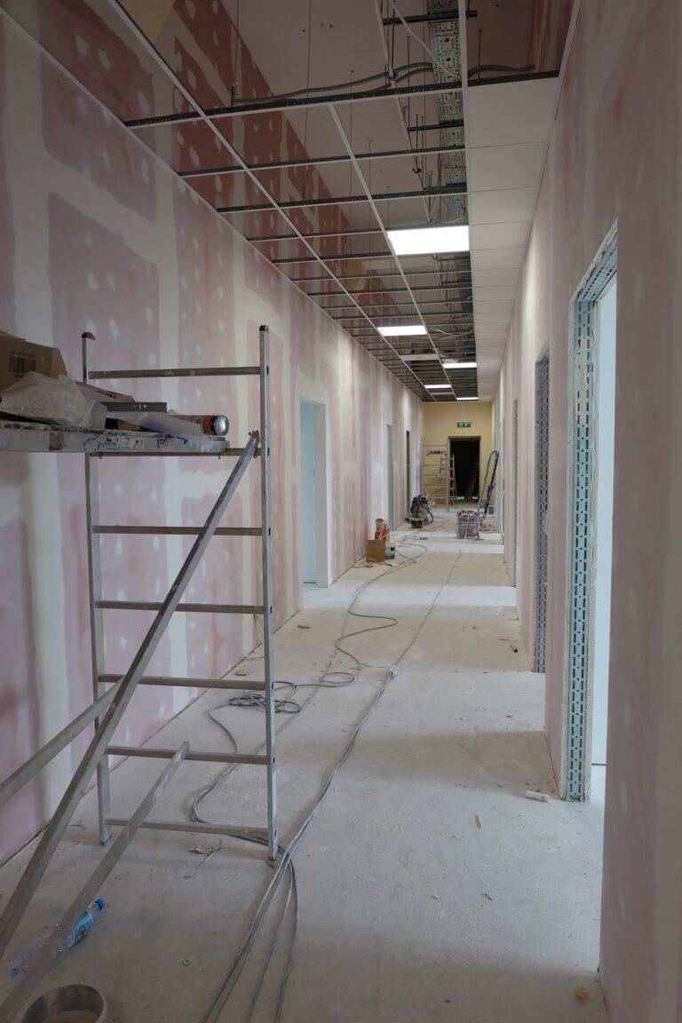 Na zdjęciu widać korytarz w czasie remontu. ściany są w gładzi. Z przodu widać rozstawione rusztowanie.