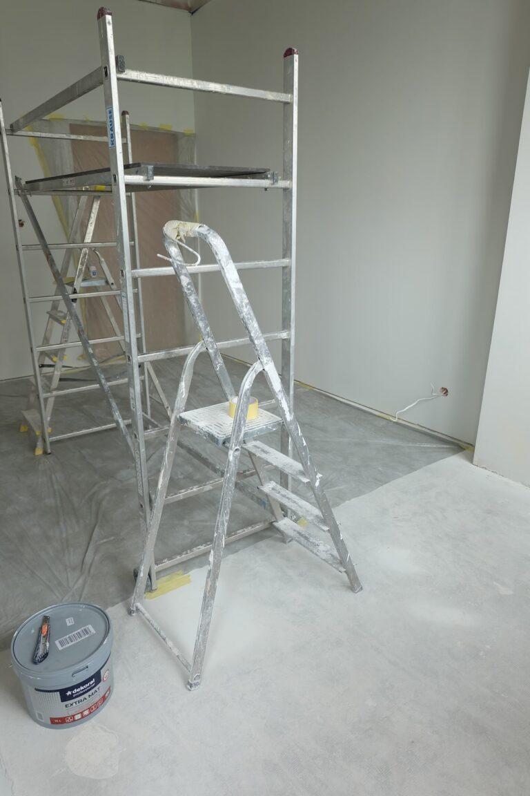 Na zdjęciu widac pokój w białych ścianach na środku jest drabina i rusztowanie na podłodze stoi wiadro