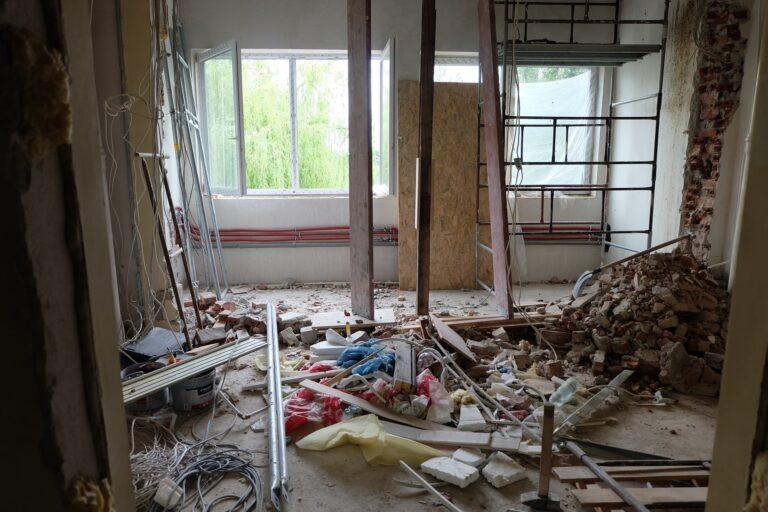 Na zdjęciu widać fragment pokoju remontowanego. są w nim rusztowania i liczne sprzęty jest tez bałagan prawdopodobnie z rozburzonej ściany