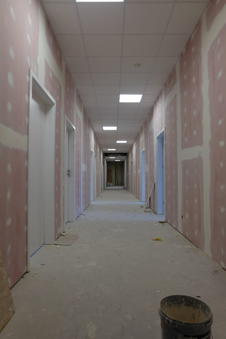 Na zdjęciu widać korytarz w czasie remontu. ściany są w gładzi. na podłodze leży wiadreko