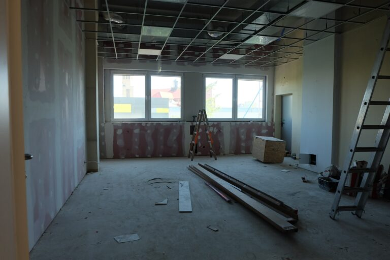 na zdjęciu widać pokój w czasie remontu są nim duże okna i 2 drabiny na podłodze są belki i wielka skrzynia