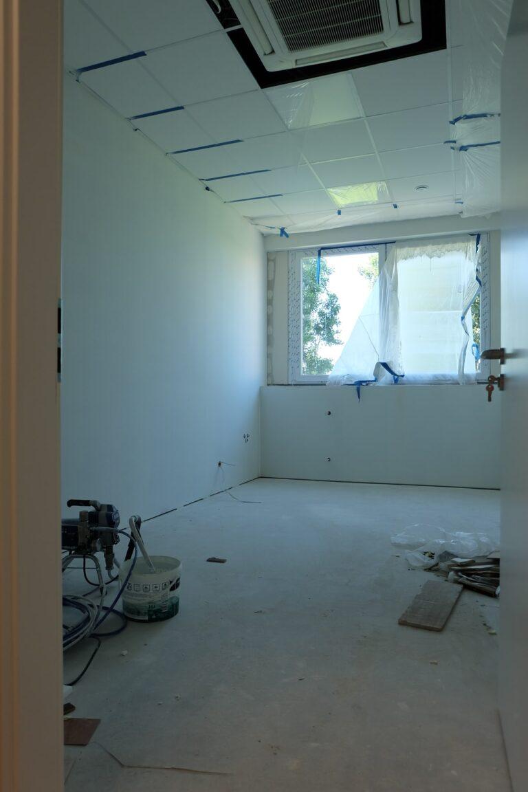 Na zdjęciu jest pokój z białymi ścianami i oknami wzdłuż jednej z nich. Pokój jest w remoncie. Na podłodze leżą narzędzia