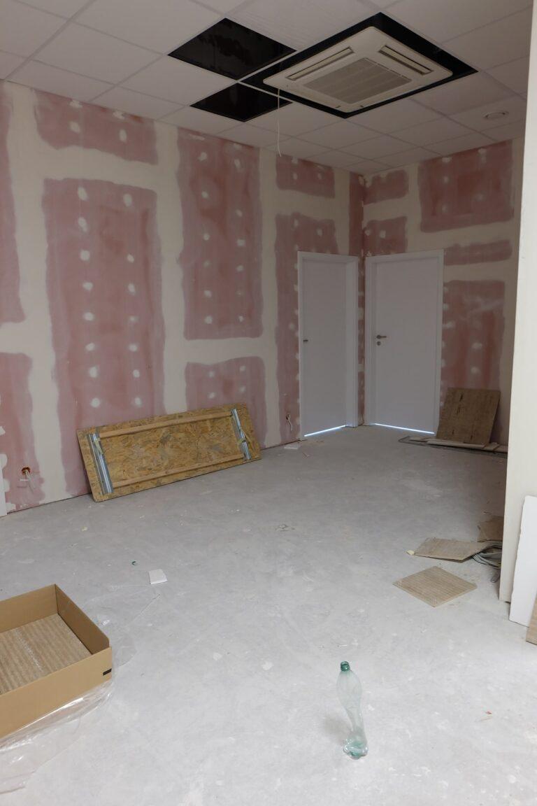 Na zdjęciu widać fragment szerszego korytarza. Są dwie pary drzwi. Ściany są w gładzi.
