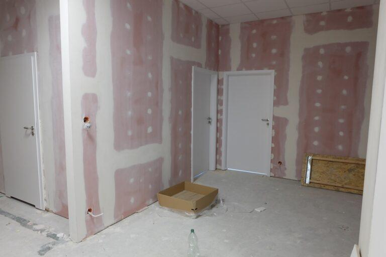 Na zdjęciu widać fragment szerszego korytarza. Są trzy pary drzwi. Ściany są w gładzi.
