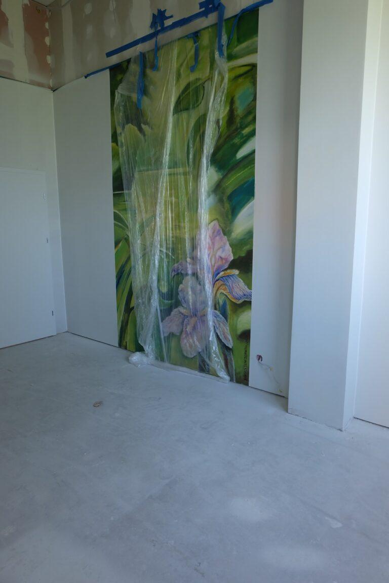 Na zdjęciu widać fragment pokoju w remoncie. Na jednej ze ścian jest namalowany duży zielony obraz z kwiatami. Jest on jeszcze w folii.