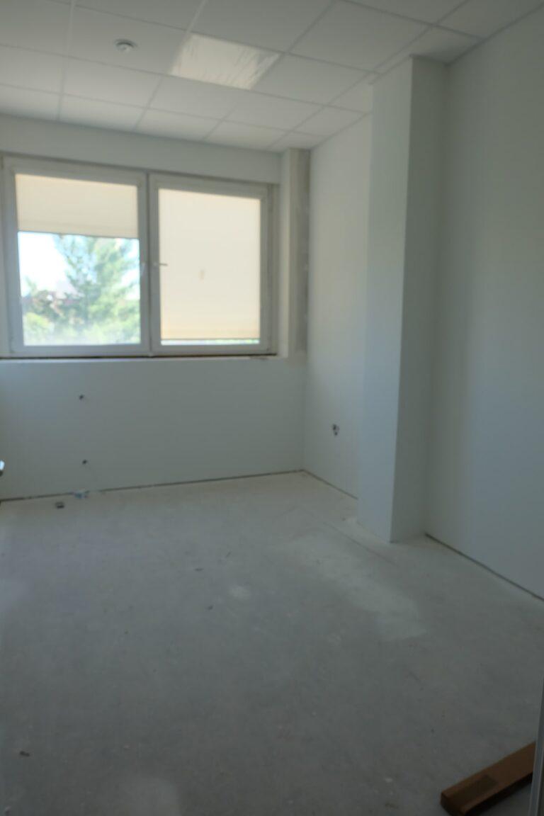 Na zdjęciu jest pokój z białymi ścianami i oknami wzdłuż jedej z nich. Pokój jest w remoncie.