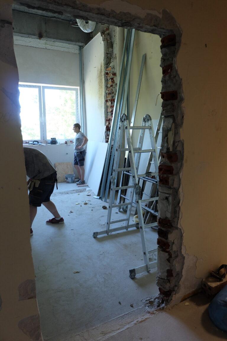 Na zadęciu widać prace remontowe, wejście do jednego z pomieszczeń oraz budowlańców. W pomieszczeniu znajduje się rozłożona srebrna drabina.