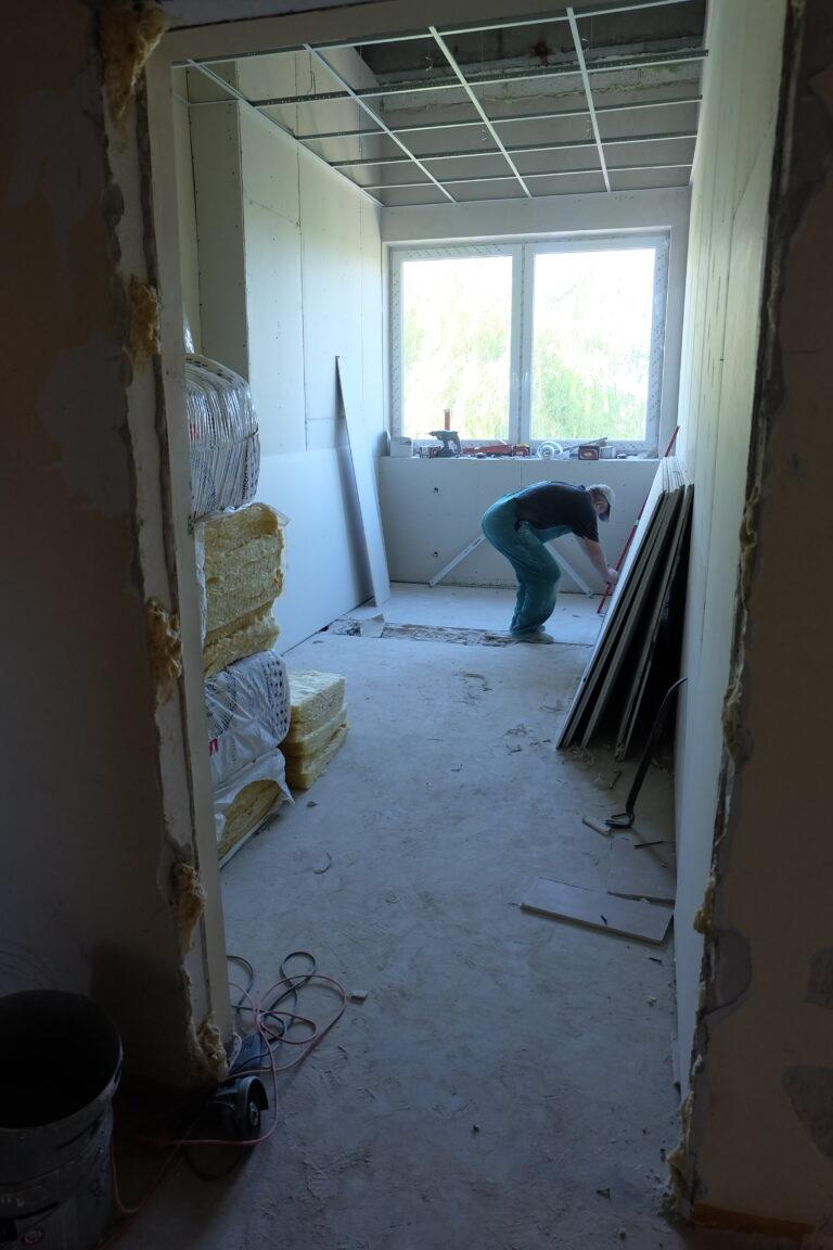 Na zdjęciu widać remontowane pomieszczenie oraz robotnika trzymającego w prawej ręce czerwona poziomnicę.