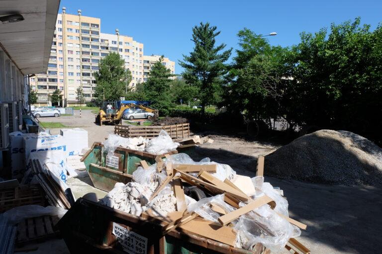 Na zdjęciu widać dwa kontenery z gruzem, folią i tekturą przed budynkiem centrum.