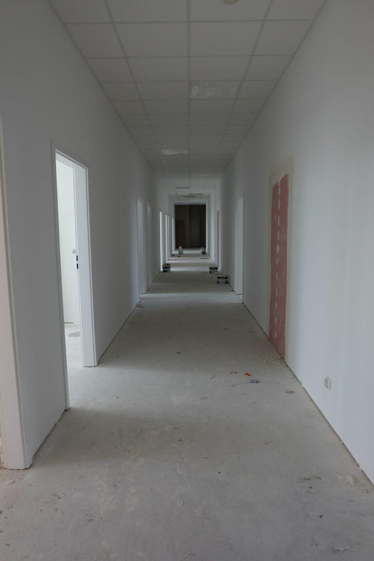 Na zdjęciu widać biały korytarz, który jest w remoncie. Wzdłuż ścian po obu stronach znajdują się drzwi gabinetów. Na podłodze rozstawione są wiaderka z farbą.