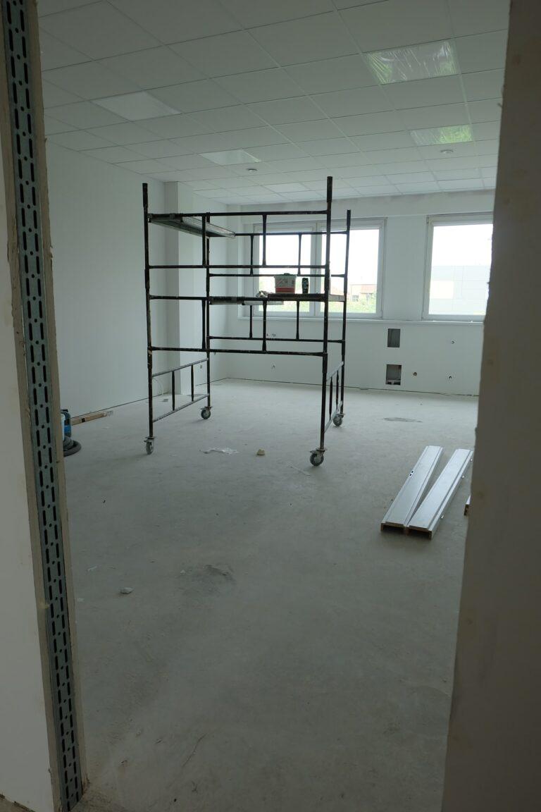 Na zdjęciu przedstawiony jest pokój z białymi ścianami i oknami naprzeciwko wejścia. Pokój jest w remoncie. Na środku jest rozstawione rusztowanie.
