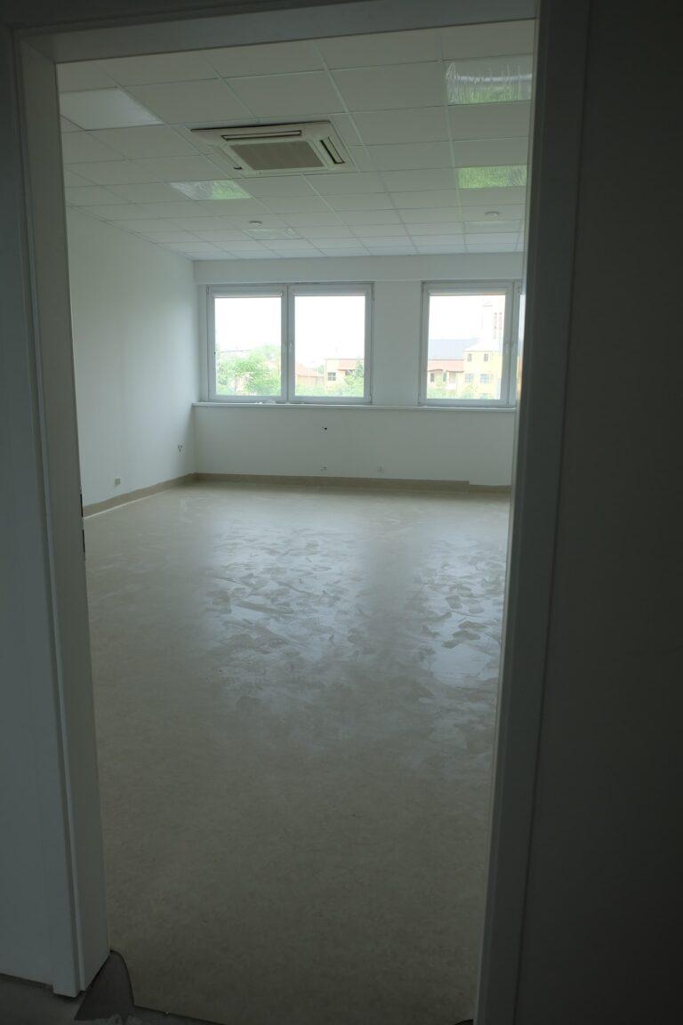 Na zdjęciu przedstawiony jest pokój z białymi ścianami i oknami naprzeciwko wejścia. Pokój jest w remoncie.