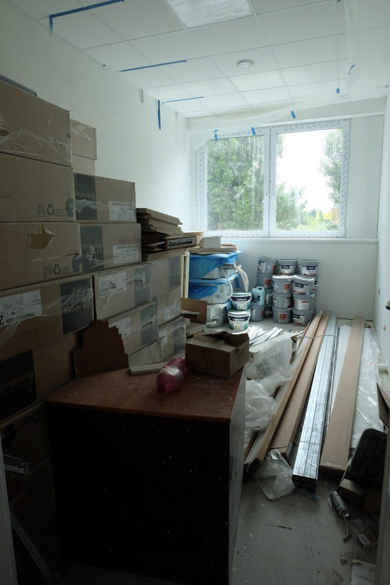 Na zdjęciu widać pokój z białymi ścianami i oknami na jednej ze ścian. W pokoju znajdują się kartony, wiaderka z farbami oraz inne narzędzia i materiały budowlane.