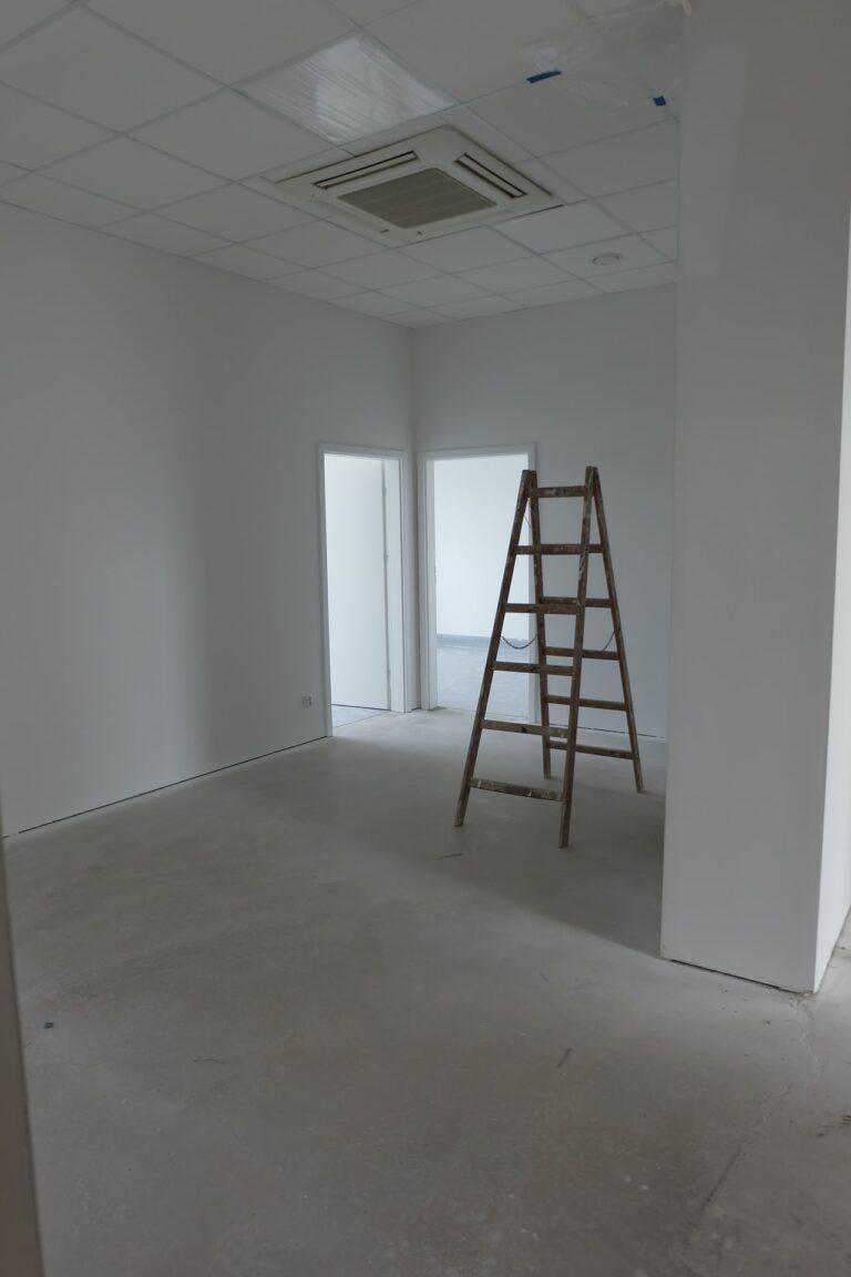 Na zdjęciu znajduje się wnętrze jednego z gabinetów. Pokój jest w remoncie, ma białe ściany. Na środku jest rozstawiona drabina.