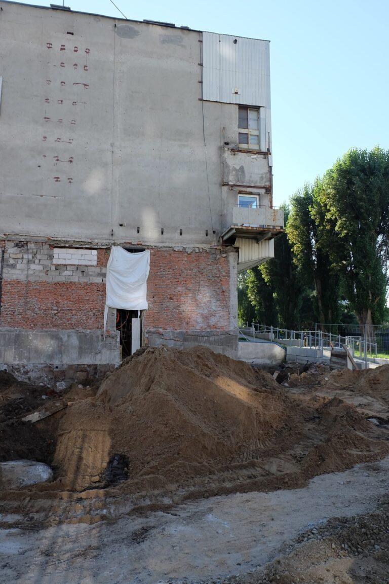Na zdjęciu widać budynek Centrum z zewnątrz. Jest on W remoncie i widać cegły. Przed budynkiem są górki z piaskiem.