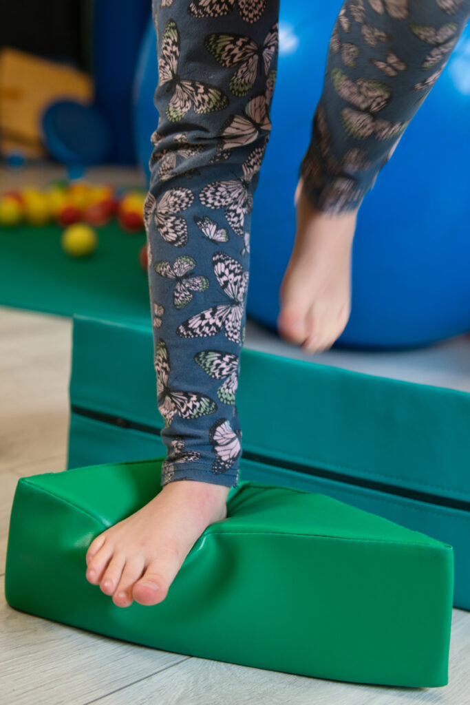 Na zdjęciu widać bose nogi dziecka. Schodzi ono z turkusowego materaca. Lewą nogę ma delikatnie uniesioną do góry. natomiast prawa stopa położona jest na zielonym miękkim klocku. Dziecko ubrane jest w turkusowe legginsy w różowe motylki. W tle widoczna jest niebieska piłka oraz zielona mata, a na niej rozsypane kolorowe piłeczki.