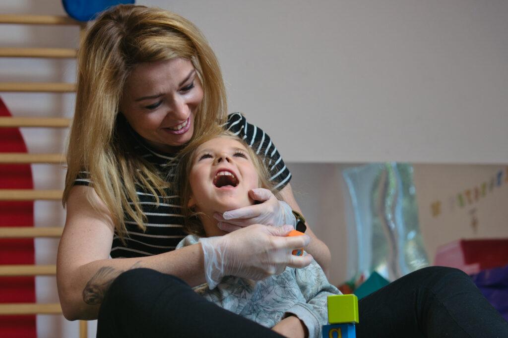 Zdjęcie przedstawia kobietę obejmującą małą dziewczynkę. Obie osoby siedzą na podłodze. Osoby są uśmiechnięte. Terapeutka ma ubrane jednorazowe rękawiczki oraz czarny t-shirt w białe paski. Dziewczynka oparta jest plecami do terapeutki, która podtrzymuje jej głowę. W tle widać drabinki