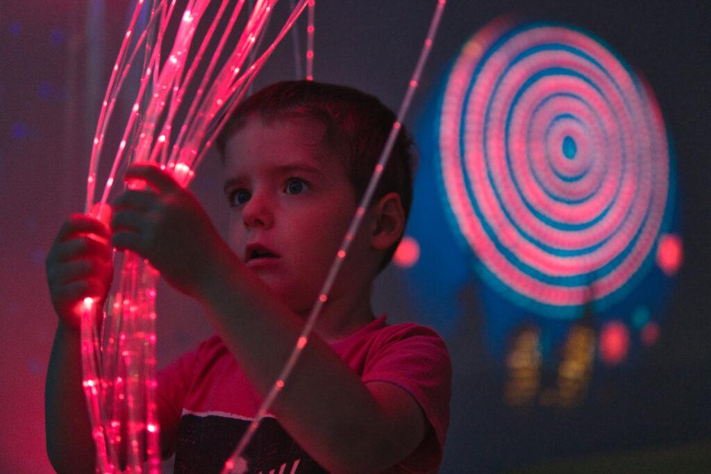 Zdjęcie przedstawia chłopczyka znajdującego się w sali Snozelen. Dotyka on zwisających ledów.