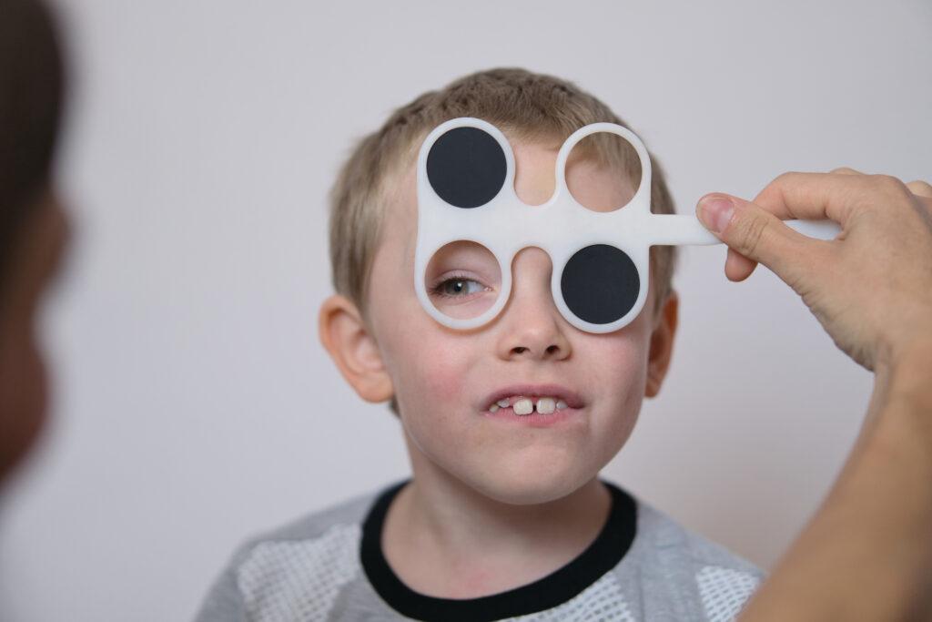 Na zdjęciu widać chłopczyka, który jest poddany badaniu wzroku. Chłopczyk jest badany specjalnym urządzeniem, które zasłania mu jedno oko. Po prawej stronie widać rękę lekarza