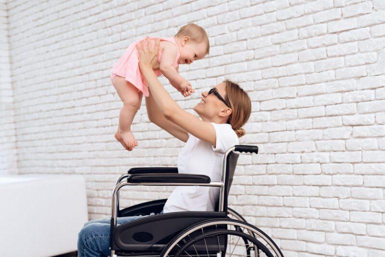 Na obrazku widać mamę na wózku inwalidzkim trzymającą uniesioną nad sobą małą dziewczynkę ubraną w różową sukienkę. Mama uśmiecha się do dziecka, a dziecko odwzajemnia jej uśmiech. Tło jest białą sianą złożoną z małych, dekoracyjnych cegiełek.