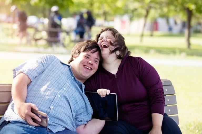 Na zdjęciu widać dwójkę uśmiechniętych ludzi siedzących na ławce. Jest to kobieta i mężczyzna. Ich twarze są widocznie rozbawione. Mężczyzna jest oparty o kobietę i w prawej ręce trzyma telefon. Prawdopodobnie robi selfie. Mężczyzna ubrany jest w niebieską koszulę na krótki rękaw, kobieta natomiast we fioletową zasuniętą bluzę. Obydwoje mają włosy w kolorze brązowym.