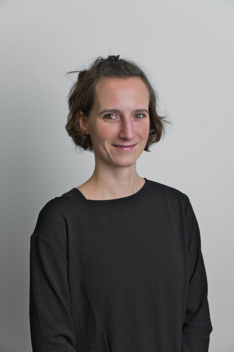 Na zdjęciu widać panią Agatę Wnukiewicz. Jest ona uśmiechnięta ma krótkie brązowe włosy ubrana jest w szarą koszulkę jest na białym tle
