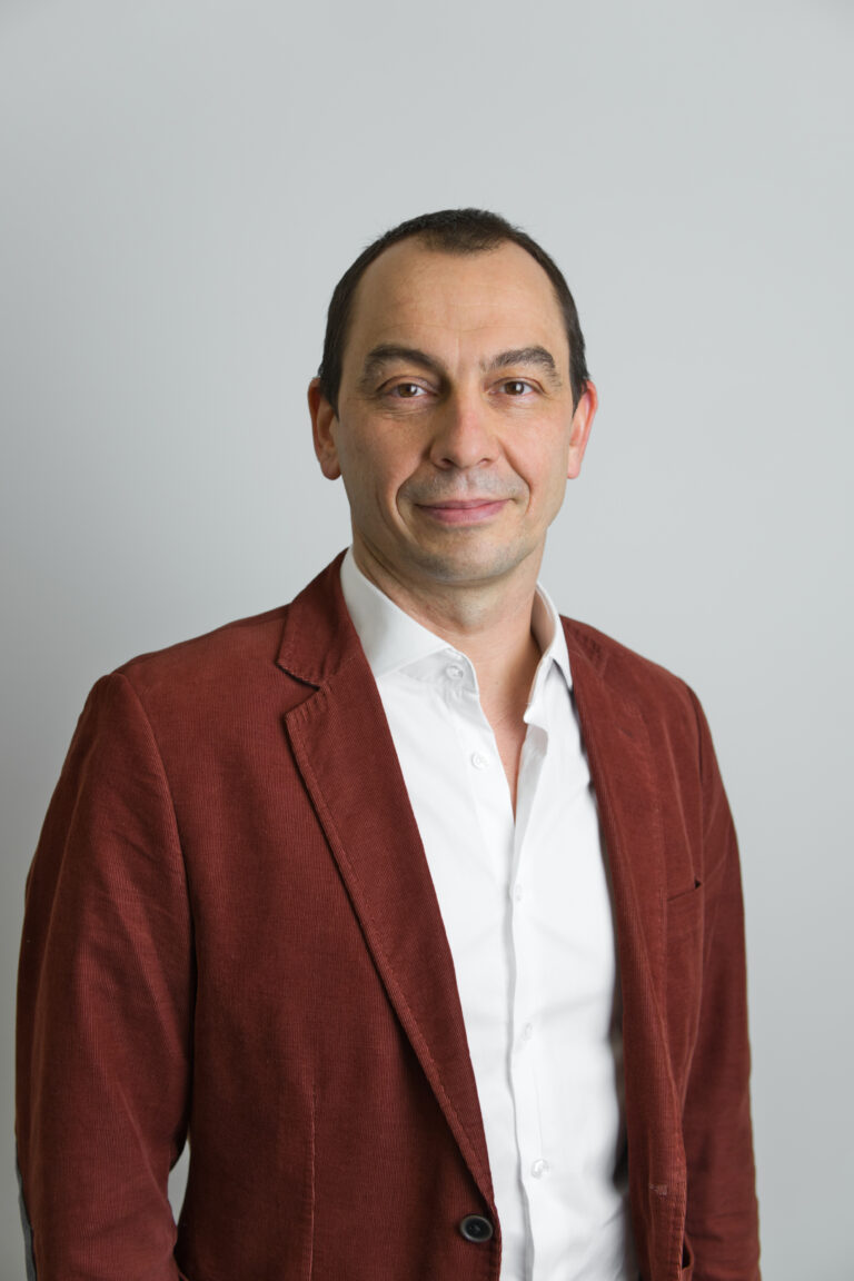 Na zdjęciu znajduje się uśmiechnięty Pan Bartosz Sikorski. Mężczyzna ma brązowe włosy. Ubrany jest w białą koszulę oraz bordową marynarkę. Znajduje się na szarym tle