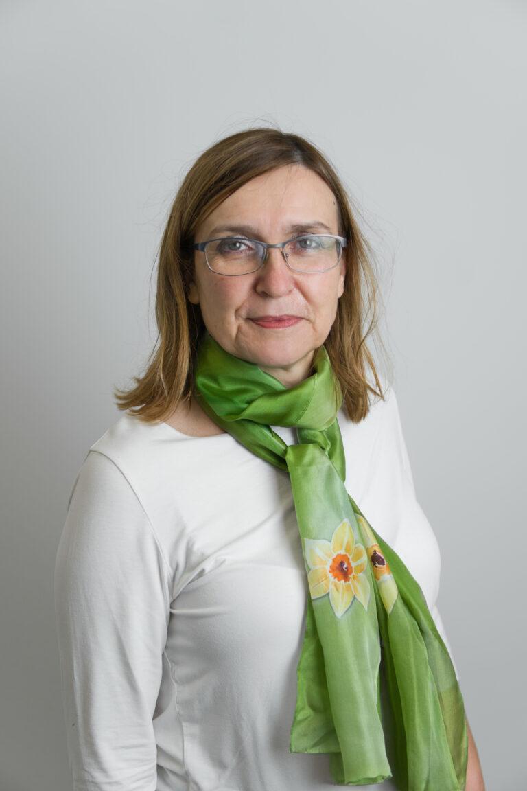 Na zdjęciu widać Panią Beatę Jędrzejczyk-Góral, znajdującą się na szarym tle. Kobieta ma blond włosy do ramion oraz srebrne okulary. Ubrana jest w białą koszulkę z długim rękawem. Na szyi kobiety znajduje się zielona chusta.