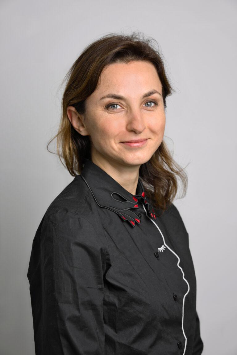 Na zdjęciu widać uśmiechniętą panią Anne Wiśniowską-Dolny, która znajduje się na szarym tle. Kobieta ma brązowe włosy do ramion. Ubrana jest w czarną koszulę z biało-czerwonymi elementami.
