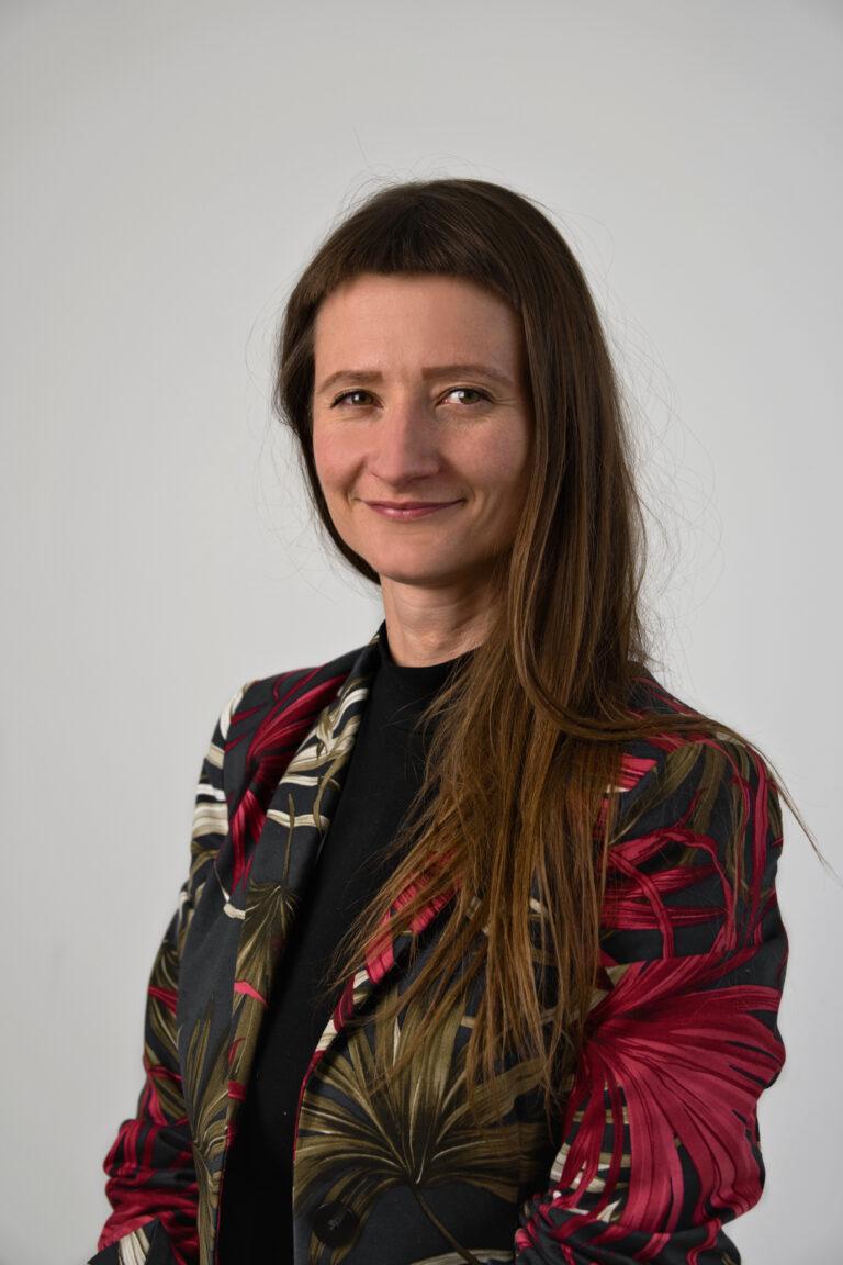Na zdjęciu widać uśmiechniętą kobiete, która ma długie brązowe włosy. Ubrana jest w kwiecistą marynarkę oraz czarną koszulkę. Znajduje się na szarym tle.