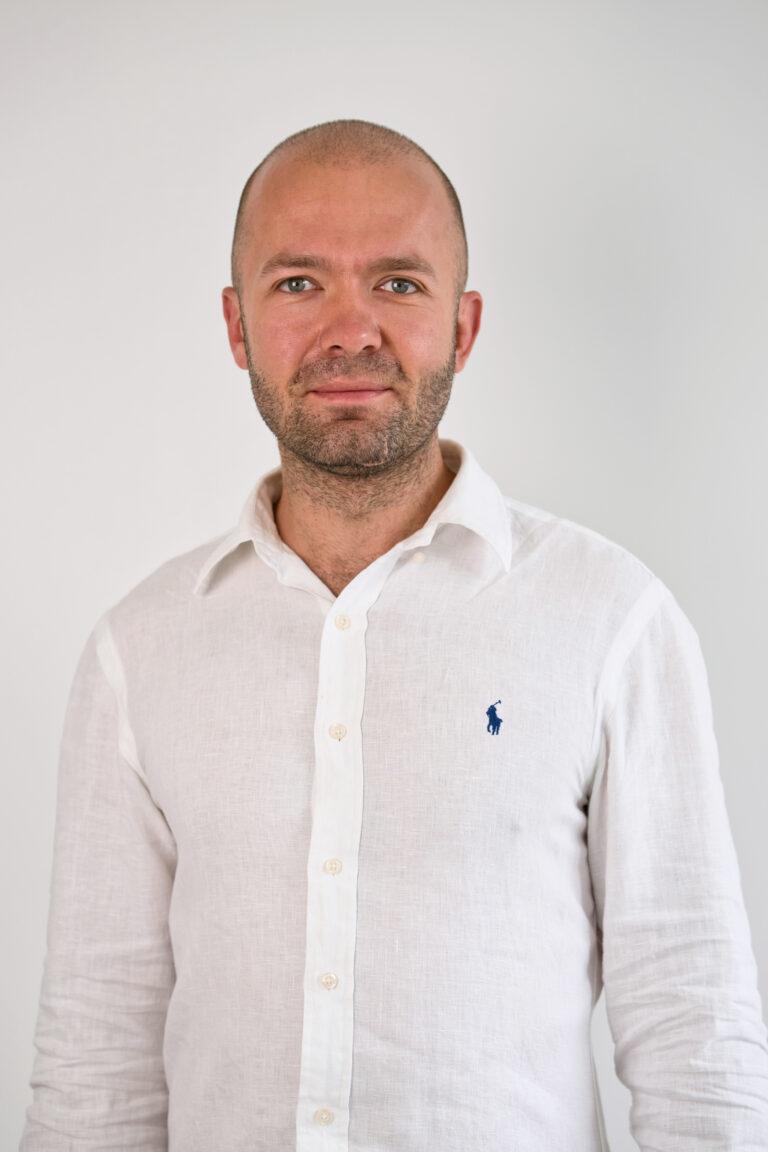 Na zdjęciu widać uśmiechniętego Pana. Mężczyzna jest łysy i posiada lekki zarost. Ubrany jest w białą koszulę. Znajduje się na szarym tle.