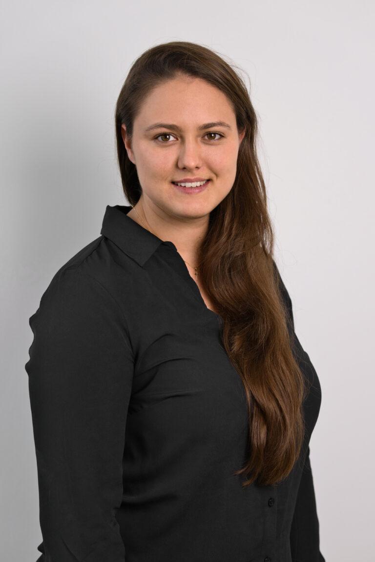 Na zdjęciu widać uśmiechniętą Panią Ewelinę Wolańską. Kobieta ma długie brązowe włosy. Ubrana jest w czarną koszulę. Znajduje się na szarym tle.