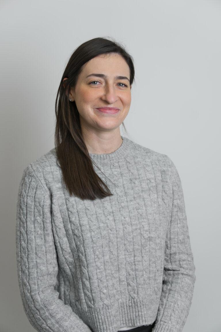 Na zdjęciu widać uśmiechniętą panią Katarzynę Gwóźdź. Kobieta ma brązowe proste włosy ubrana jest w szary sweterek i znajduje się na szarym tle