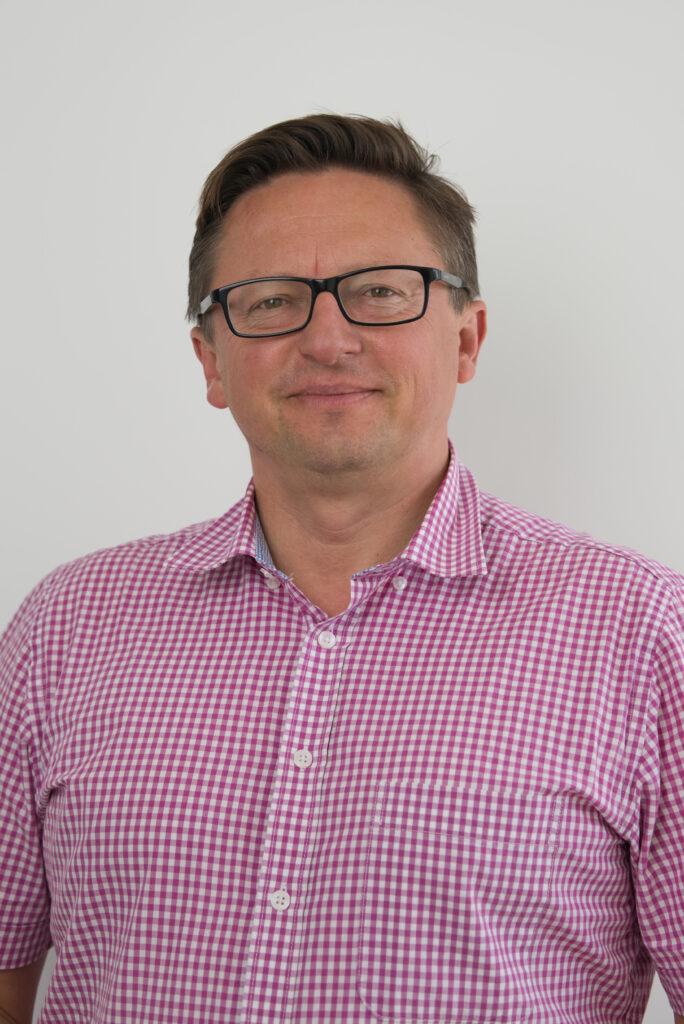 Na zdjęciu znajduje się uśmiechnięty Pan Robert Śmigiel. Mężczyzna ma czarne okulary. Ubrany jest w koszulę w różową kratę. Znajduje się na szarym tle.