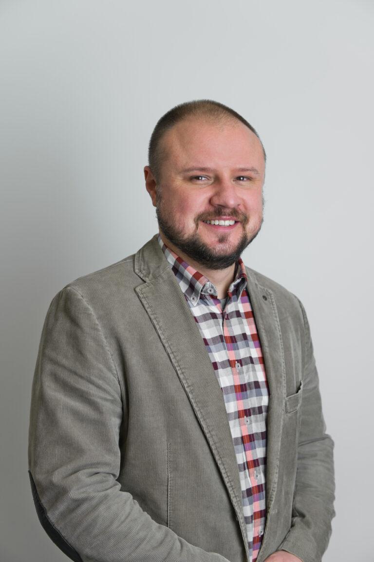 Zdjęcie przedstawia uśmiechnietego pana Witolda Wnukiewicza Mężczcyzna znajduje się na szarym tle. Ubrany jest w koszulę w kratke oraz szarą marynarkę