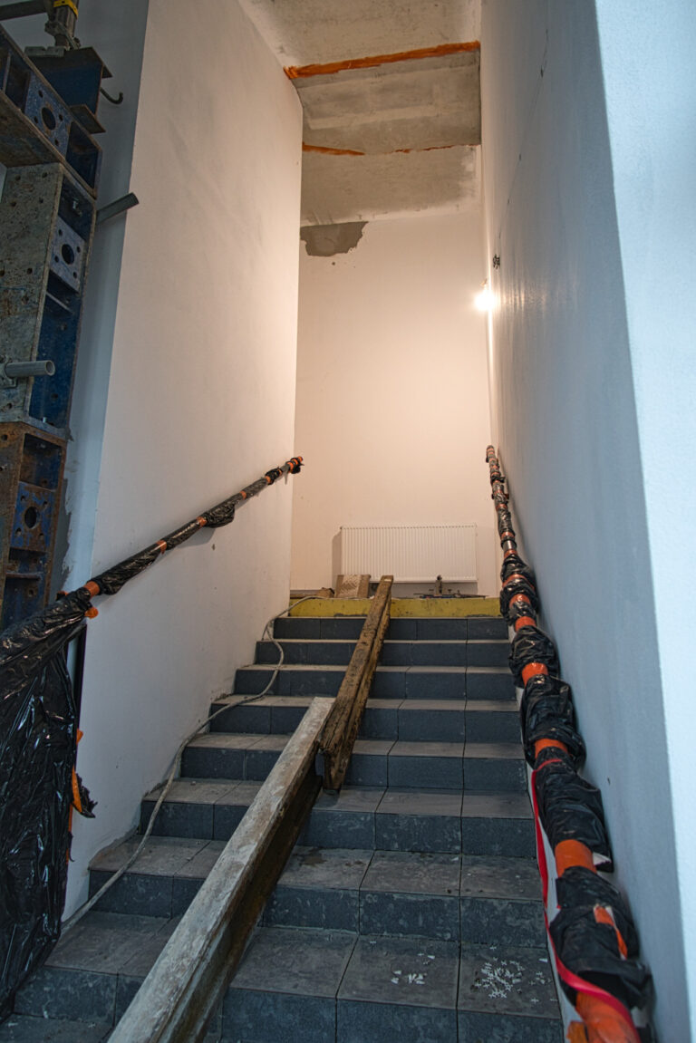 na zdjęciu widać klatkę schodową w czasie remontu na środku schodów są położone belki. na klatcce schodowej jest włączone światło