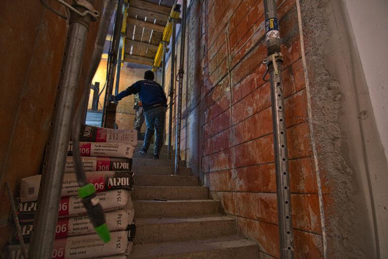 Na zdjęciu widać klatkę schodową w czasie remontu na schodach widać 2 osoby.
