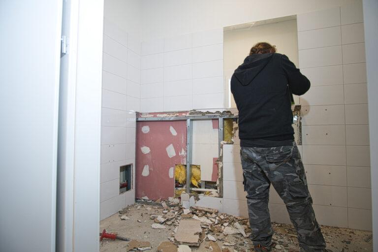 Na zdjęciu widać łazienkę w czasie remontu. Po prawej stronie widać pana robotnika od tyłu który kuje kafelki