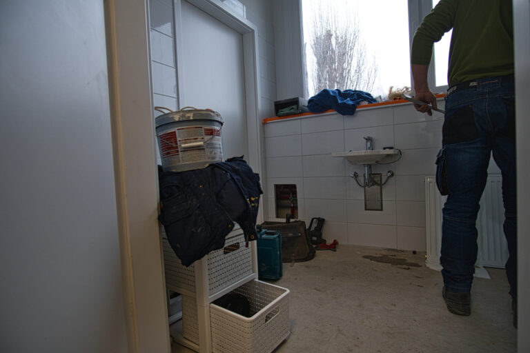 Na zdjęciu widać łazienkę w czasie remontu. po prawej stronie widać pana robotnika od tyłu