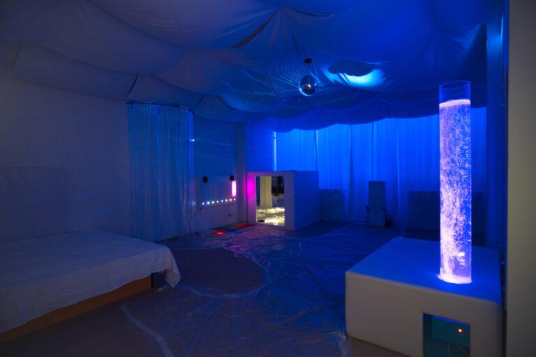 Zdjęcie przedstawia salę doświadczenia świata. Znajduje się tam łóżko wodne, lampę wodną i domek z lustrami Na podłodze jest rozłożona folia