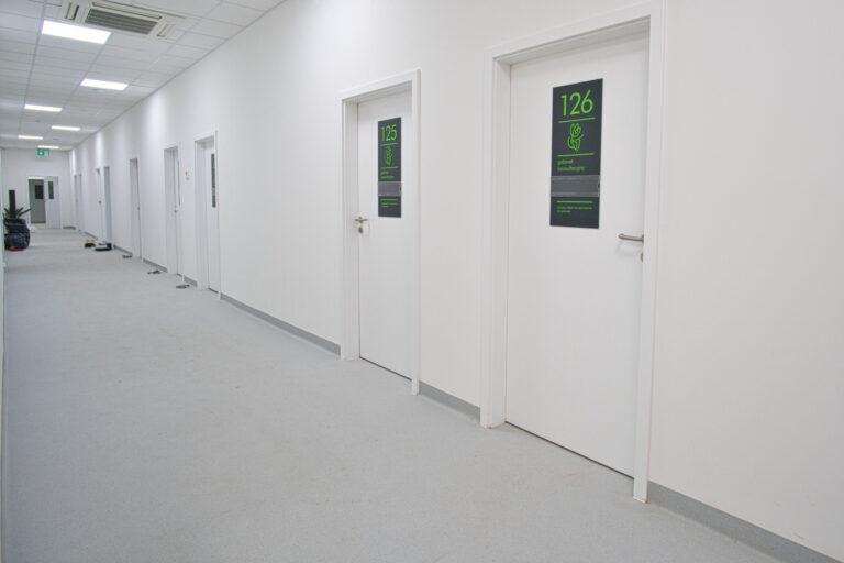 Na zdjęciu widać korytarz centrum. Ma ona szarą podłogę i białe ściany. Wzdłuż ściany są drzwi gabinetów.