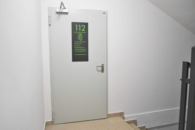 Na zdjęciu są szare duże drzwi z tabliczką z zielonym numerem 112 oraz logiem centrum