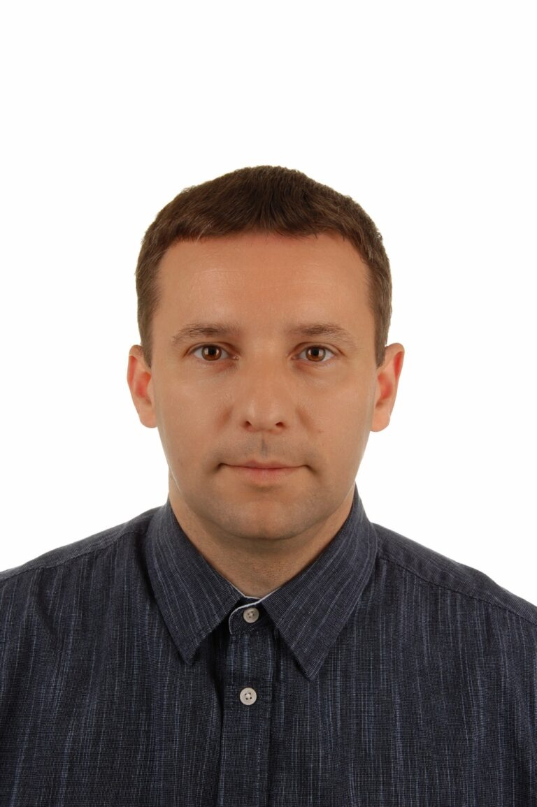 Na białym tle jest Pan Rafał Bugaj. Mężczyzna jest lekko uśmiechnięty. Ubrany jest w granatową koszulę.
